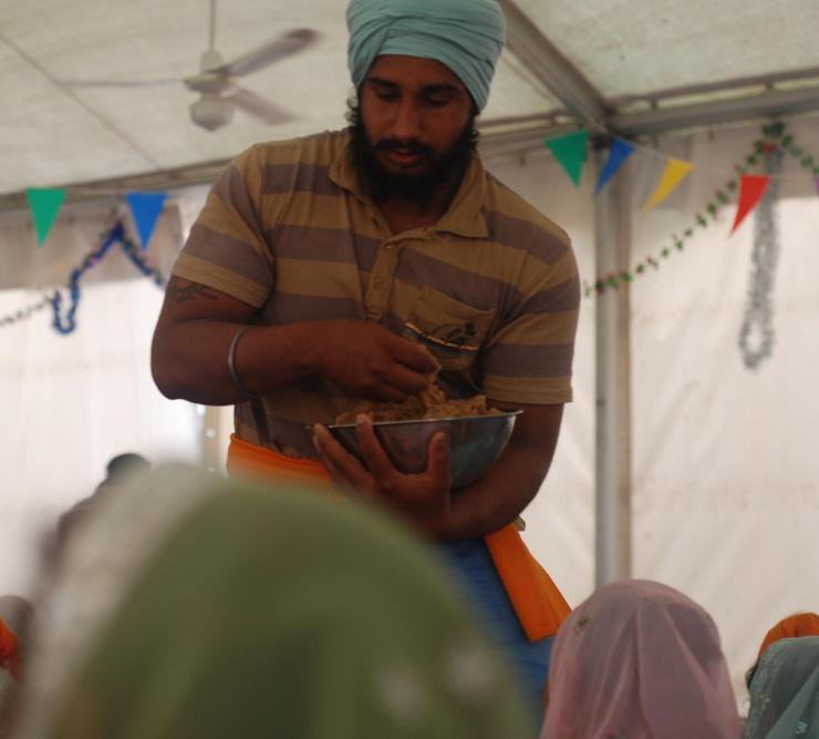 """Le geste a une connotation hautement symbolique puisque le fait de """"passer"""" de la nourriture aux fidèles est né de l'opposoition à """"la pureté"""" (pas d'aliments), typique de la tradition hindoue."""
