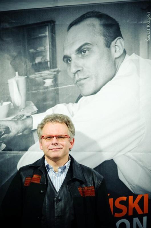 L'auteur de la biographie pose devant un portrait de Ryzsard Kapuscinsky