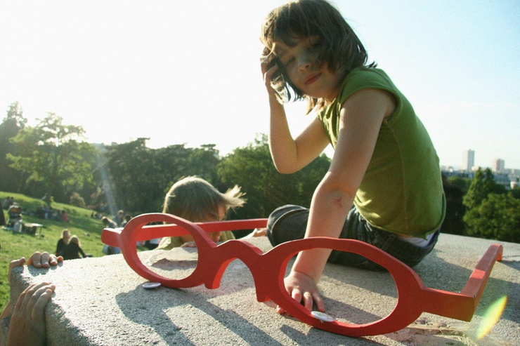 A girl plays with Joly's signature red glasses