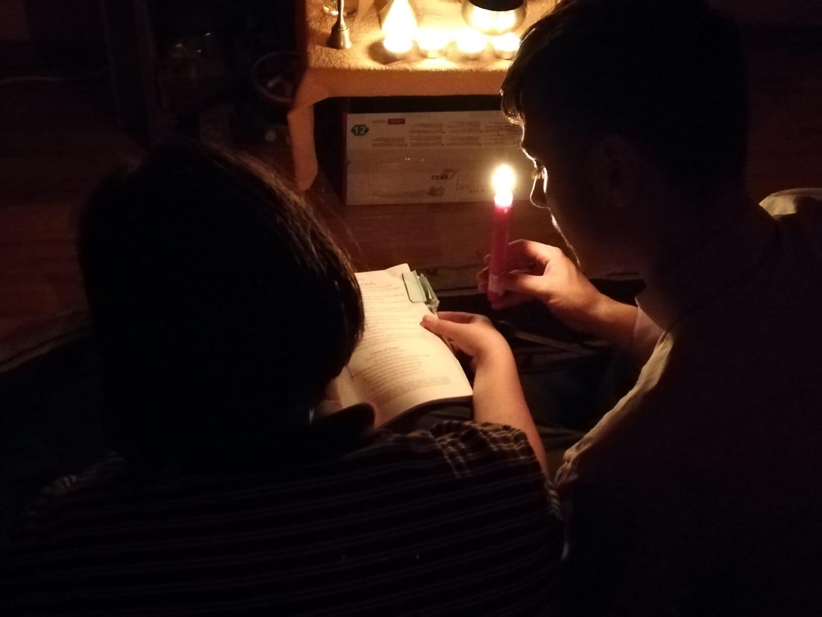 Cosmin et Mona récitent leurs prières, éclairés par des bougies © Grégoire Dao